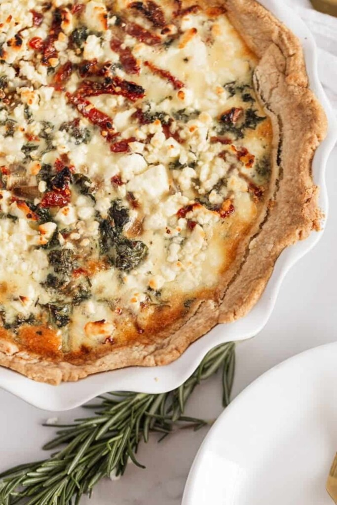kale and sundried tomato quiche next to rosemary close up