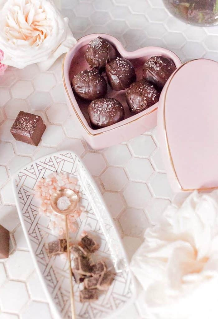salted dark chocolate truffles in a heart shaped box on a table