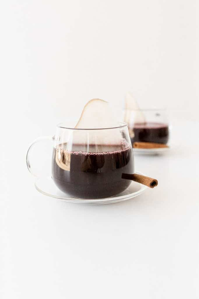 mulled wine with a pear rising from it like steam