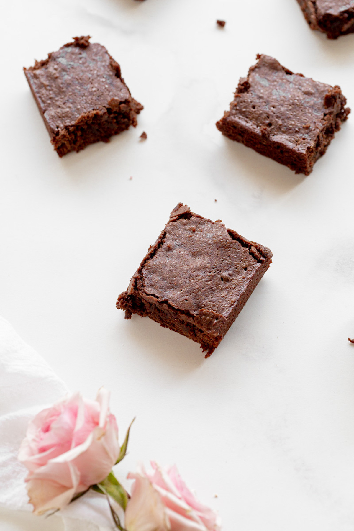 chewy brownies on marble with flowers