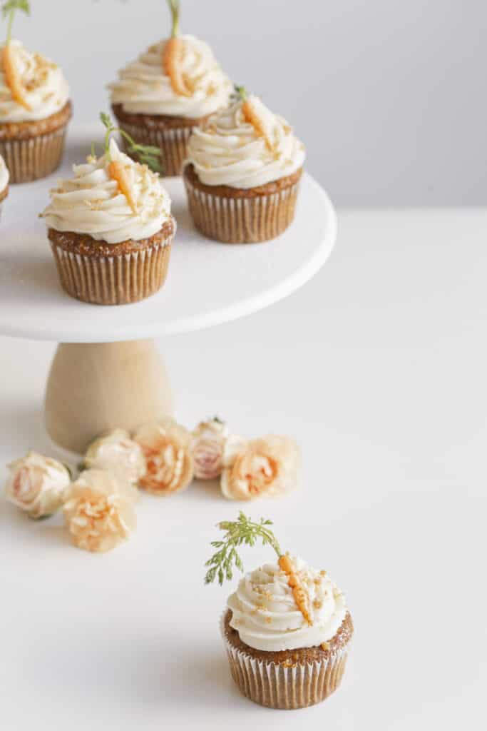 small batch carrot cupcakes on a stand with flowers and carrots
