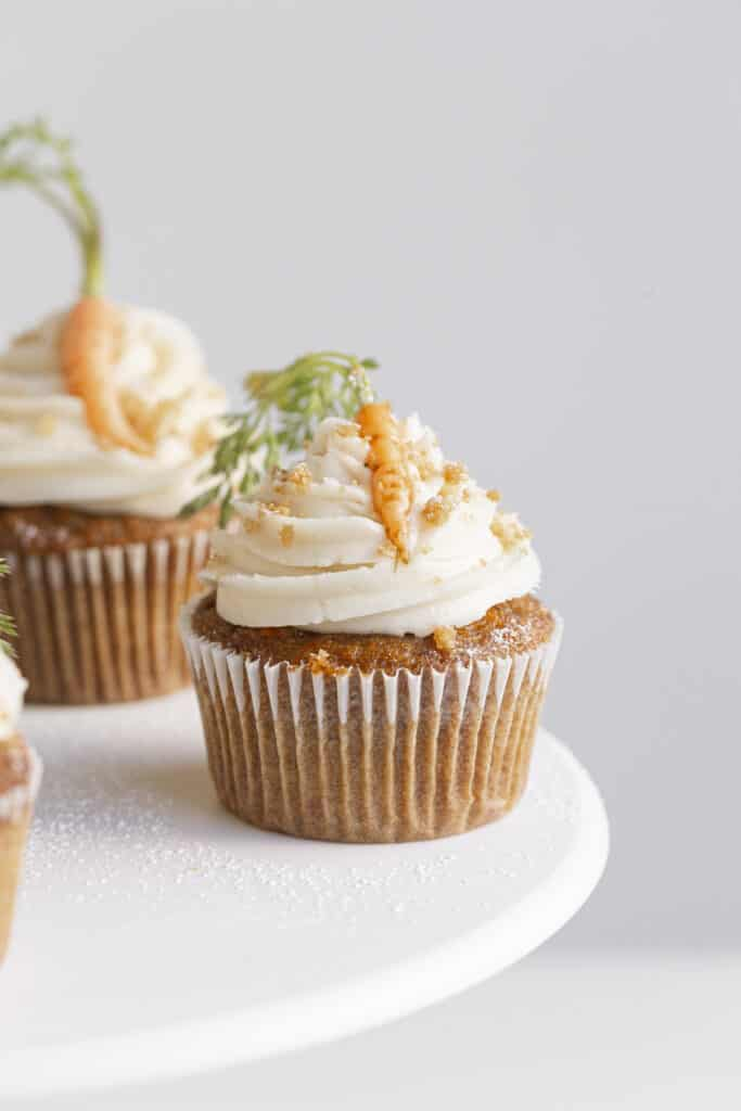 small batch carrot cake cupcakes on a stand with frosting
