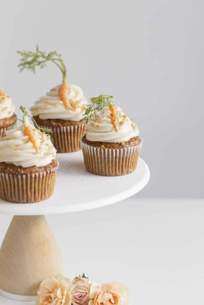 spiced carrot cupcakes on a cake stand with mini carrots and flowers