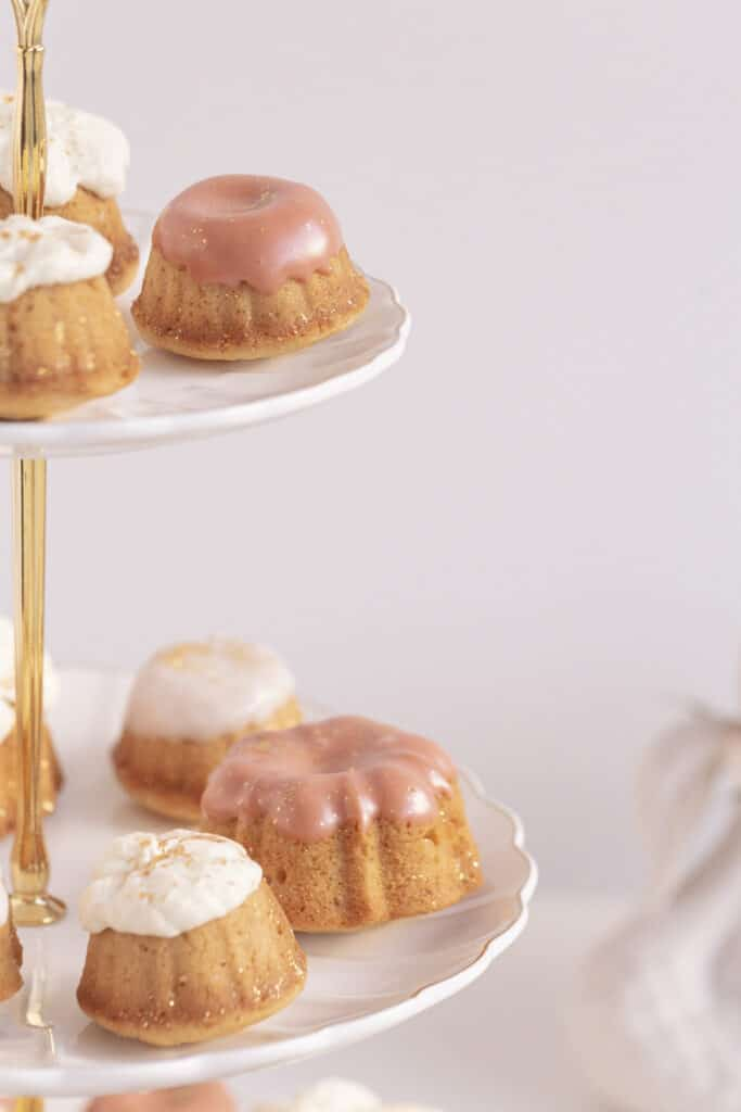honey cakes on a cake stand with pink icing and whipped cream