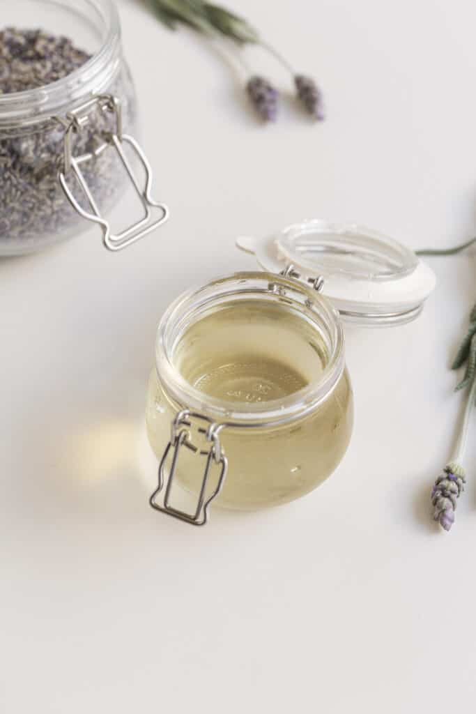 Lavender simple syrup in a jar with lavender jar and lavender flowers