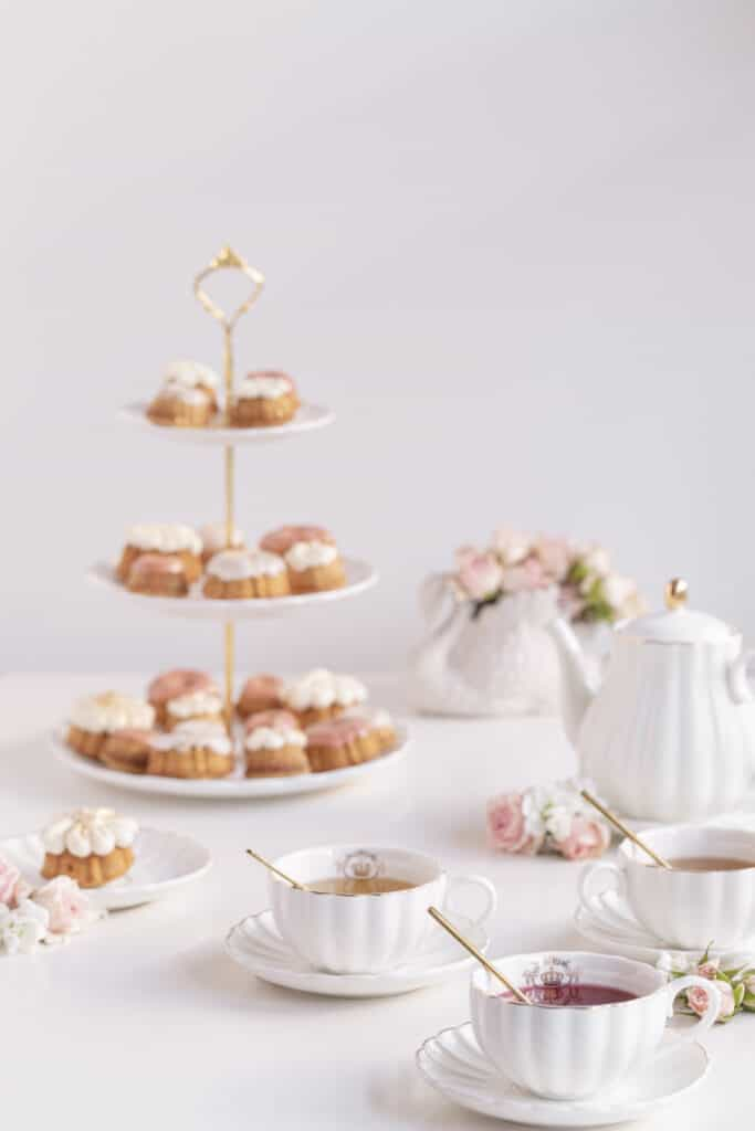 fancy tea cups and saucers with tea cakes and flowers