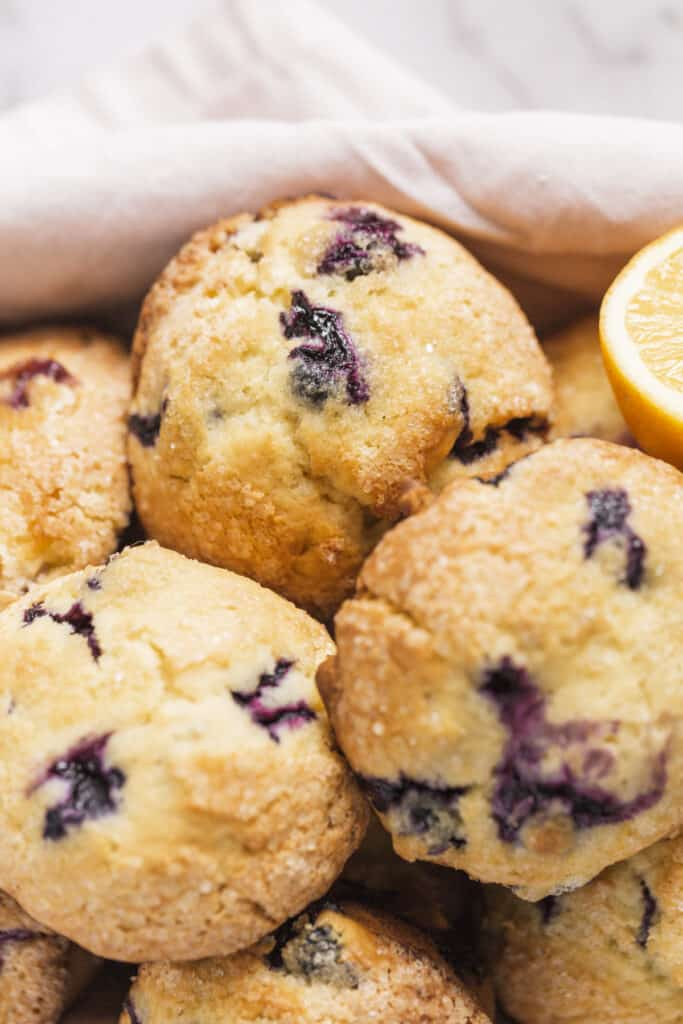 bakery style blueberry muffins in a basket with a linen and lemon