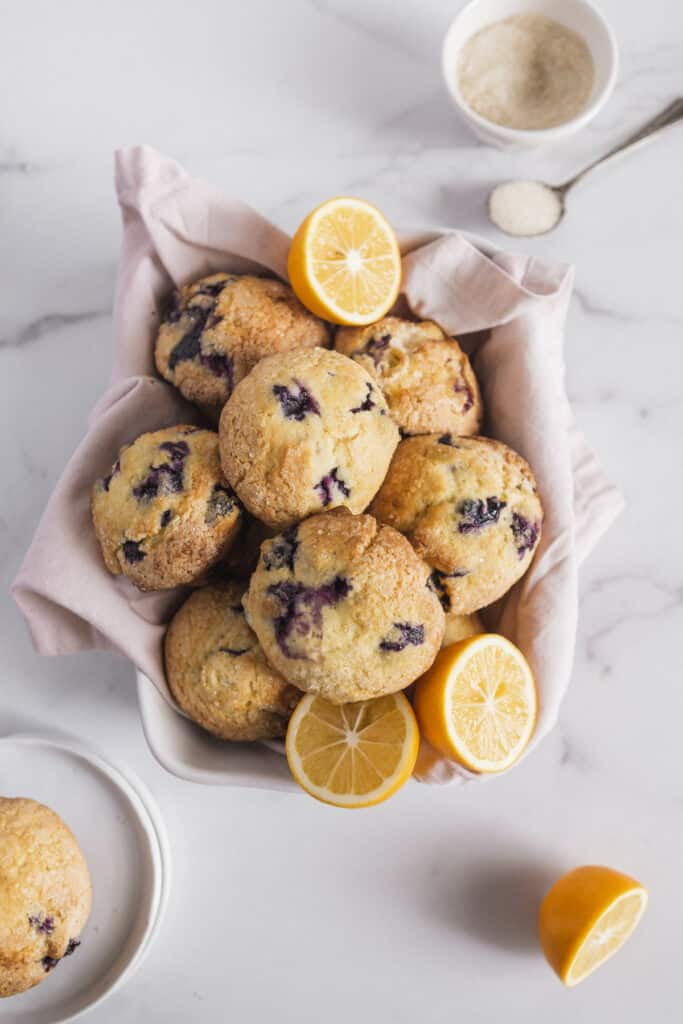 muffins piled into a basket with sugar bowl and lemon to the side