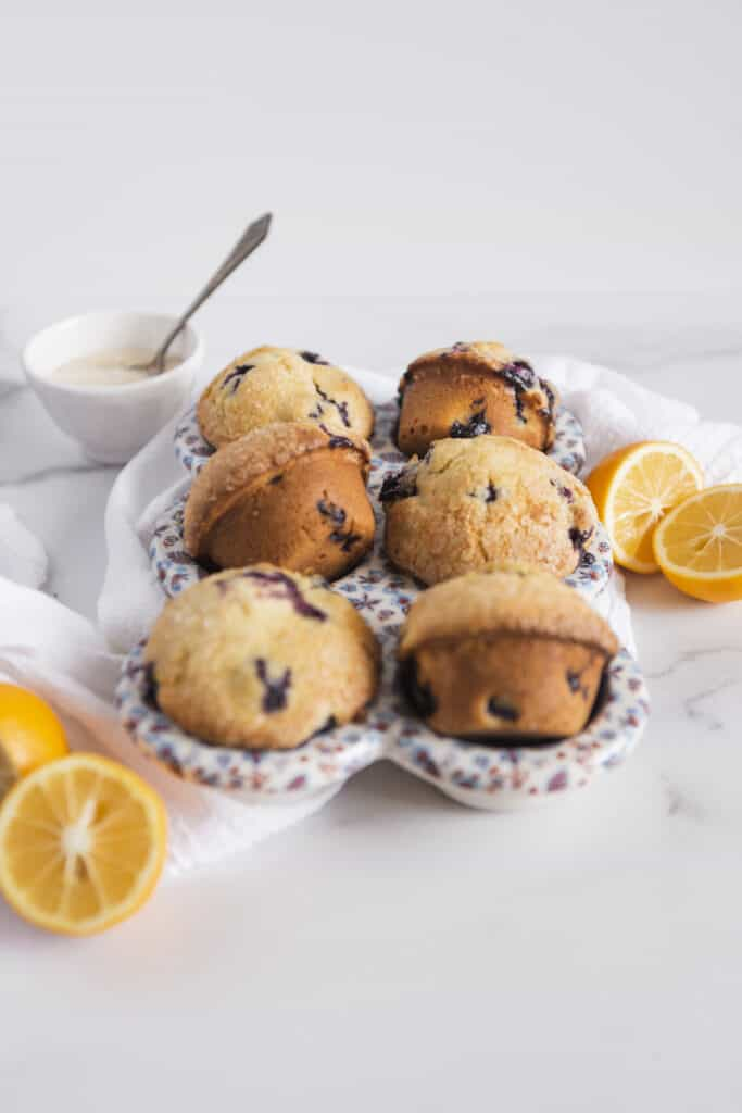 homemade muffins in a ceramic baker with lemon halves and a bowl of sugar