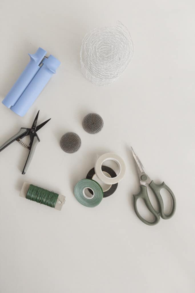 tools used for floral design at home like scissors, tape, floral frogs, rose stripper, and wire