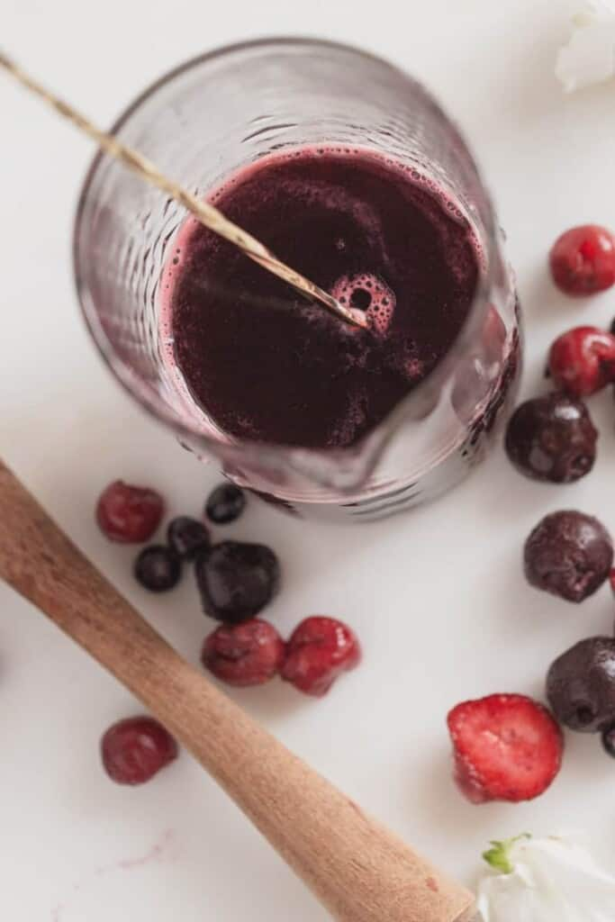 rose berry sangria in a glass with a gold straw and flowers