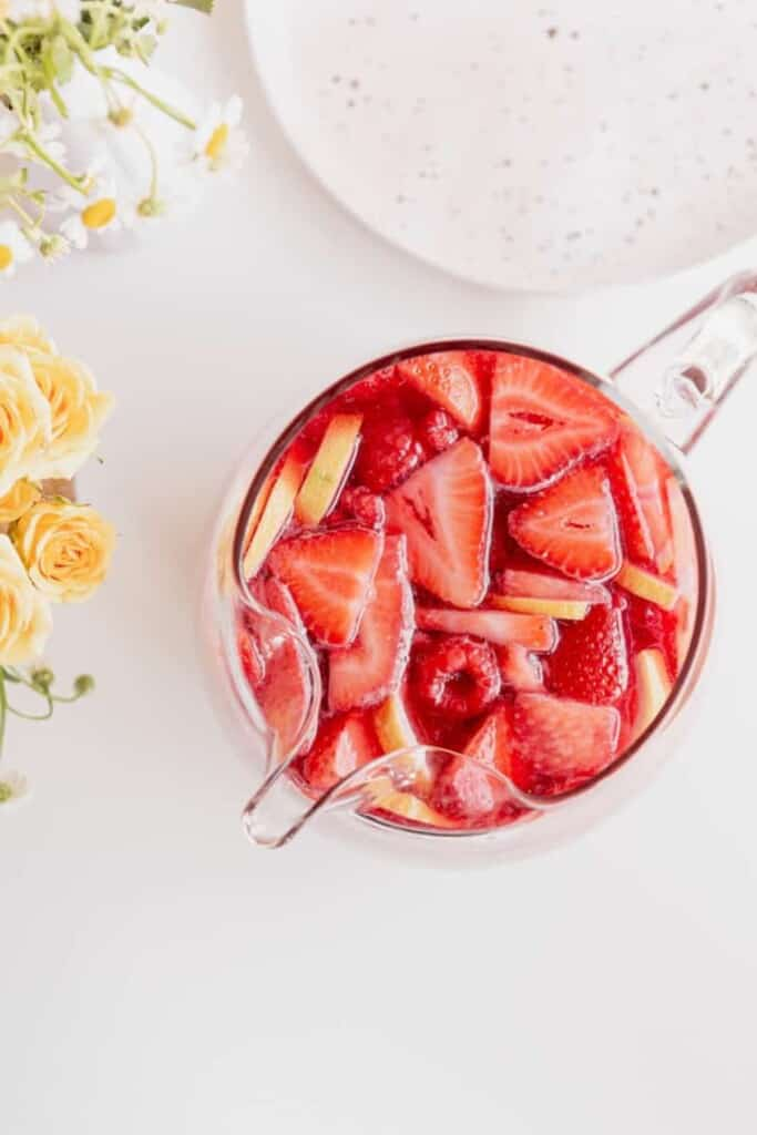 frozen berry sangria in glassware on a set table with flowers