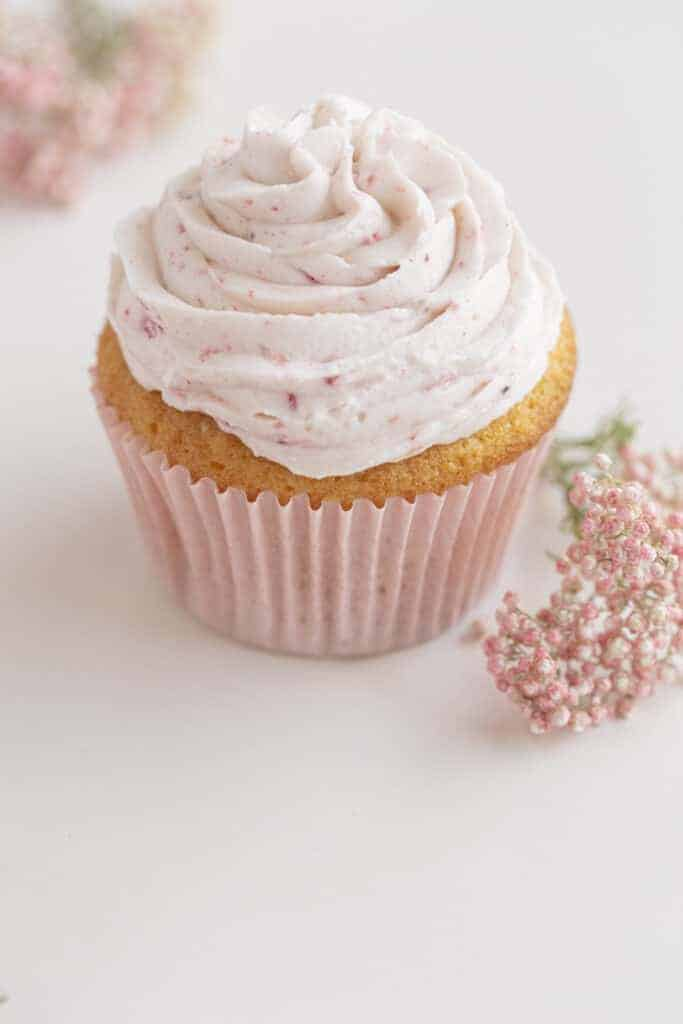 strawberry filled cupcake with pink liner and pink flowers