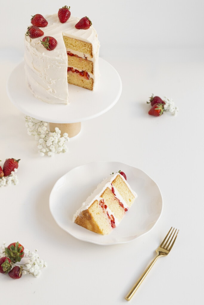 strawberry lemon cake sliced on a plate and cake on a stand