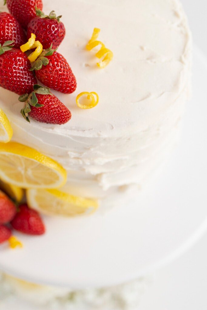 cake with strawberry filling topped with strawberries and lemon slices