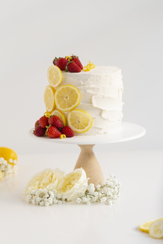 cake with strawberry filling on a cake stand with strawberries, lemons, and flowers