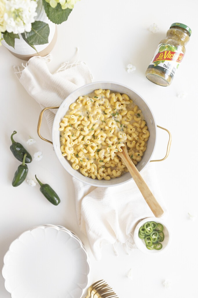 mac and cheese in a pot with jalapenos, salsa, plates and flowers