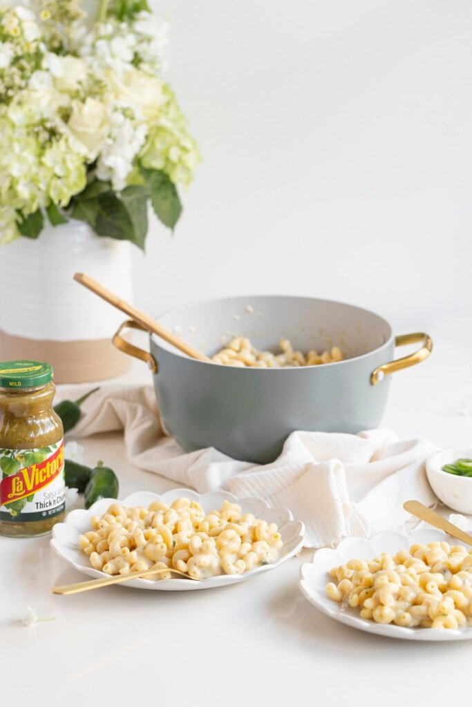 mac and cheese on plates with forks and a pot and salsa jar