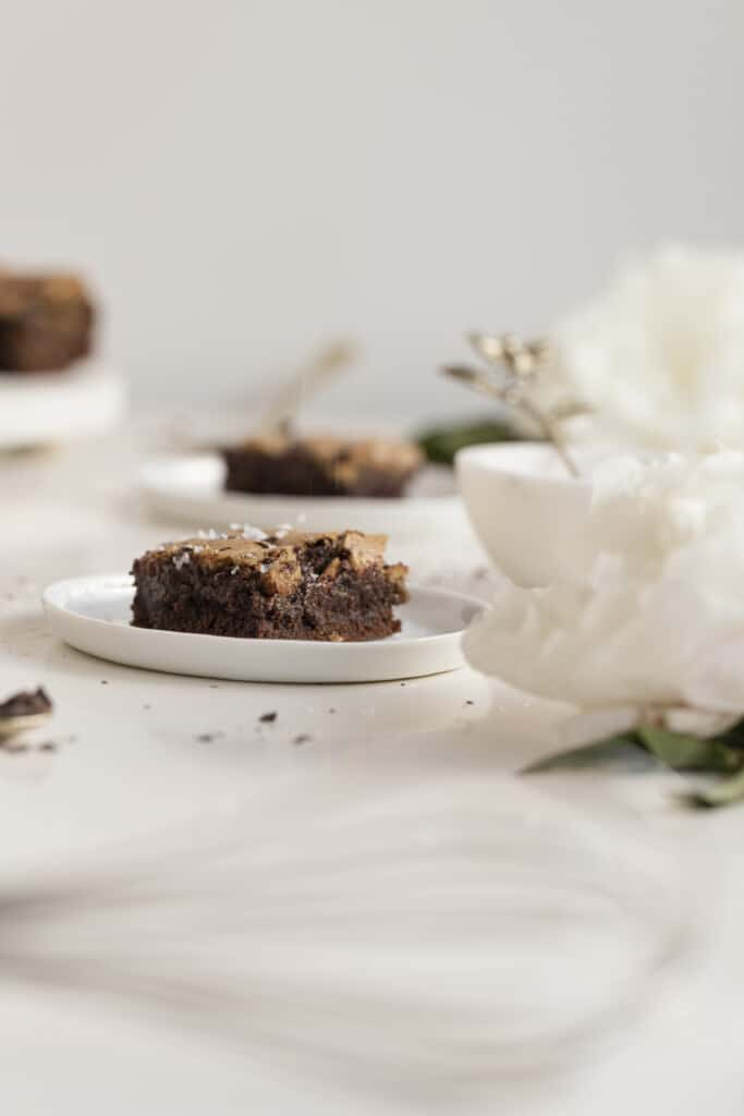 chewy fudgy chocolate brookies on a plate with flowers, chocolate, and a whisk