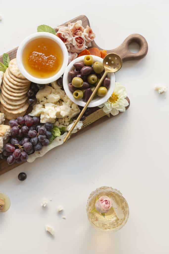 olives and honey in a bowl on a cheese board