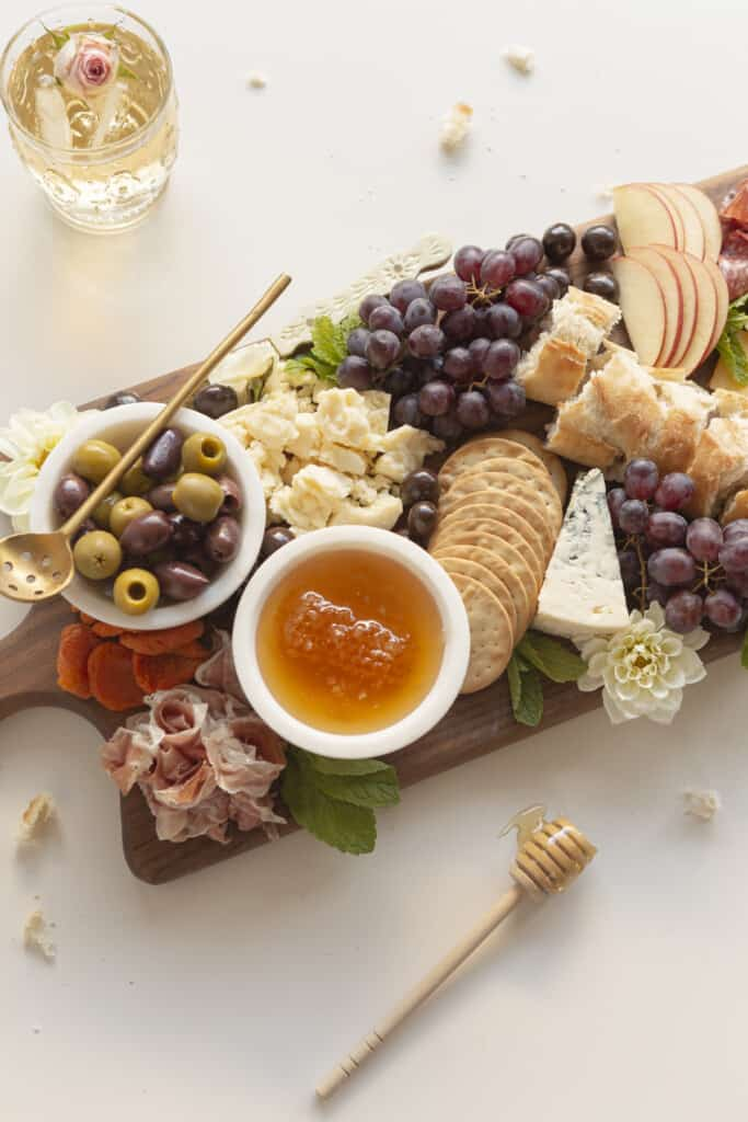 small charcuterie board with edible flowers and mint and honey
