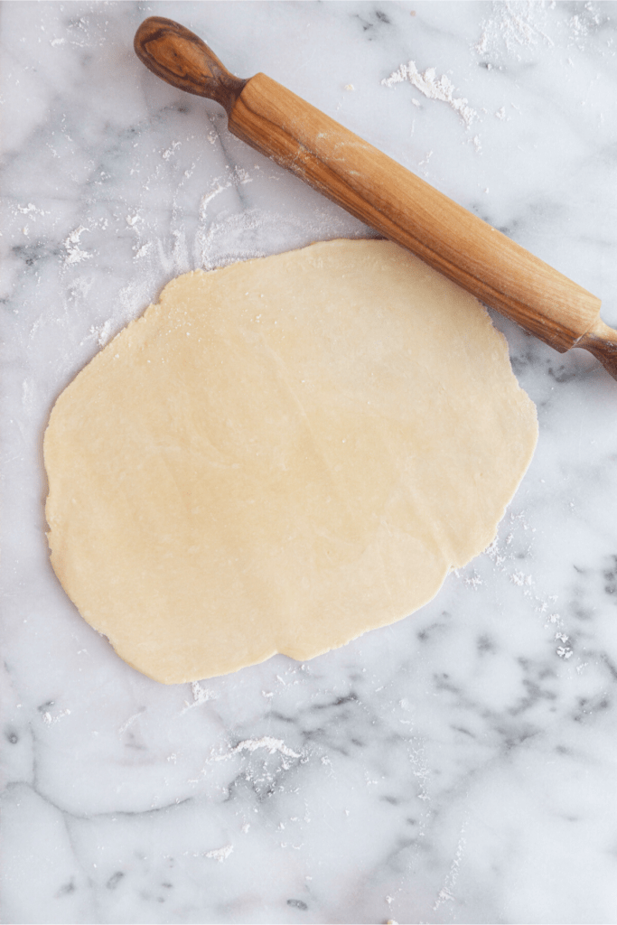pie crust rolled out on a marble surface and rolling pin