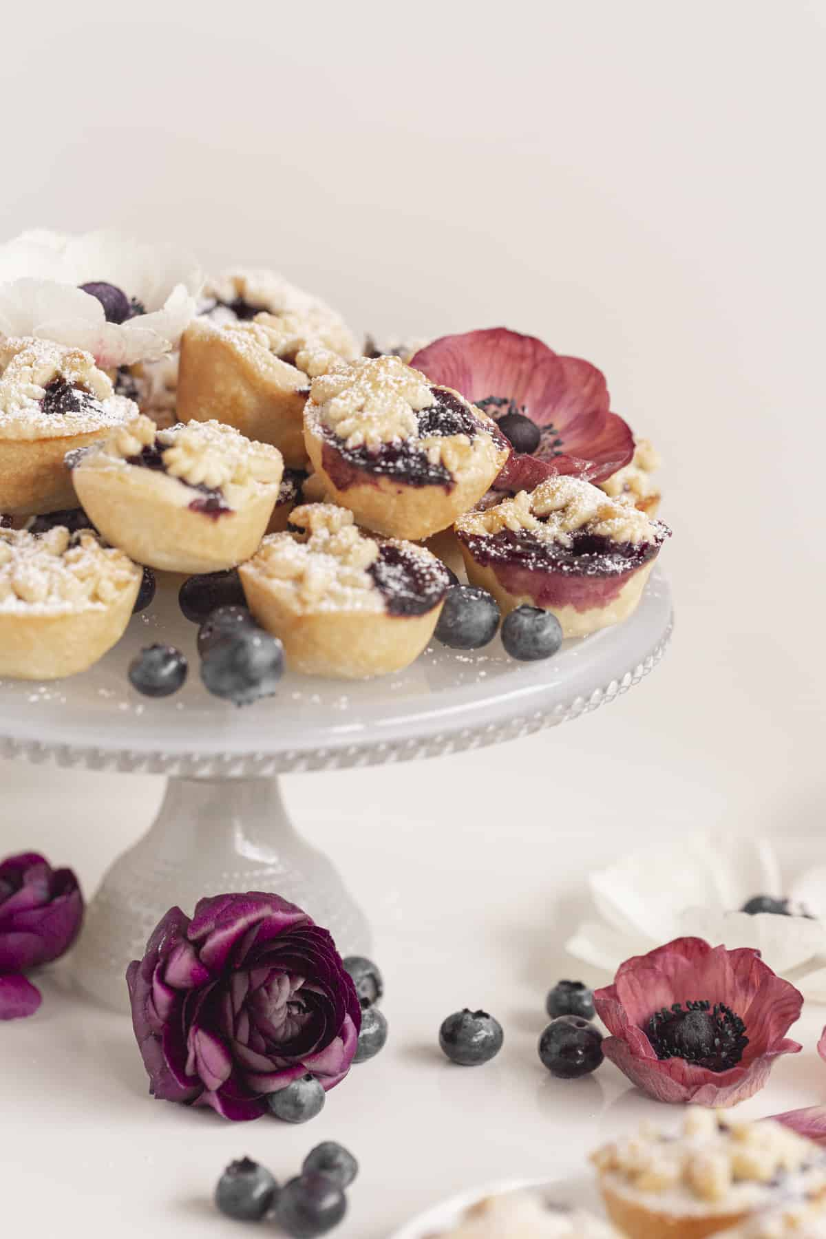 mini pies on a blue cake stand with flowers