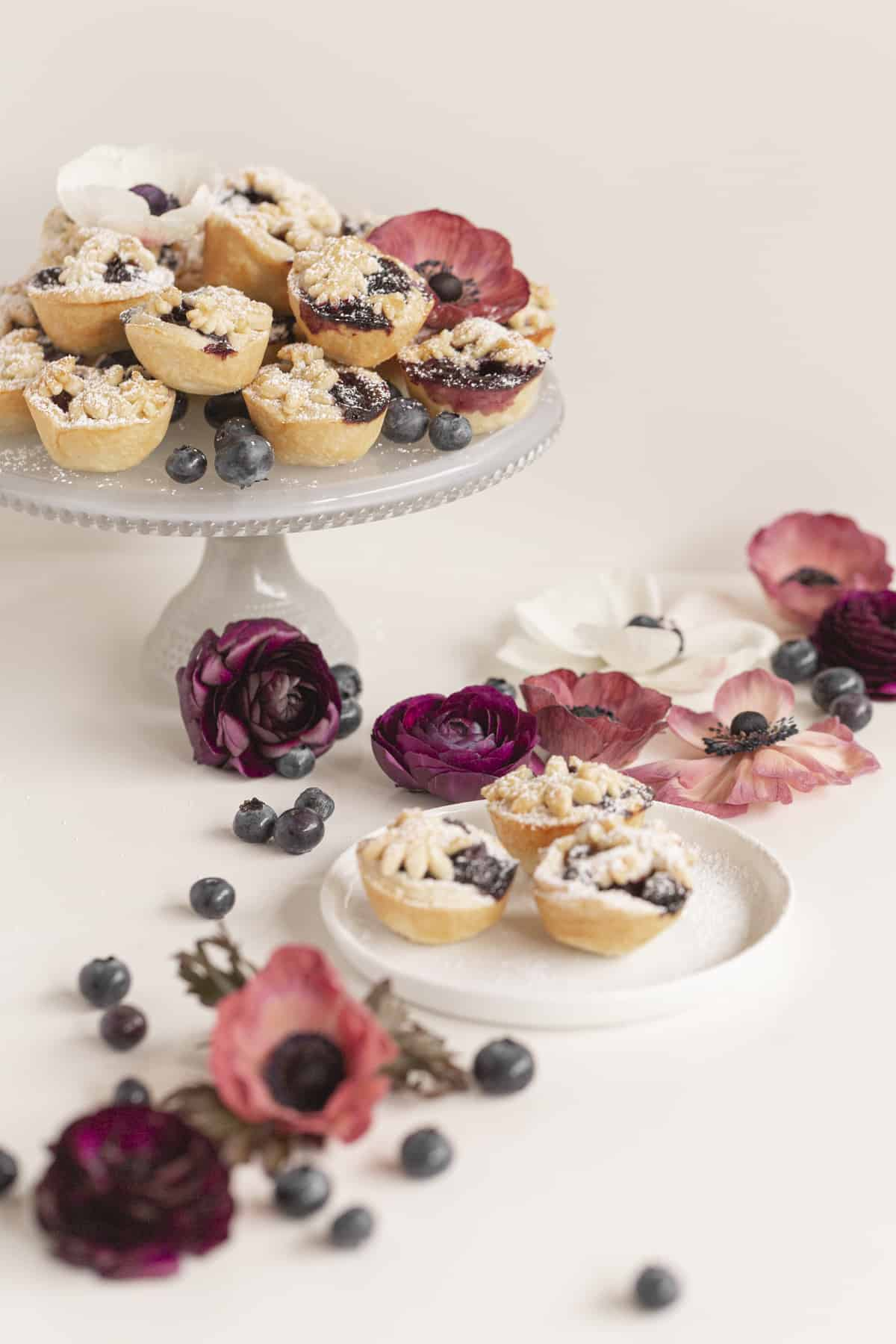 mini pies on a cake stand and plate with flowers