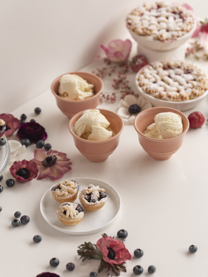 small pies with ice cream with berries and flowers on a white table