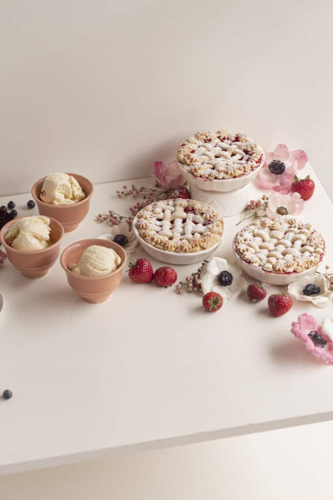 pies and ice cream in ceramics on a table with flowers