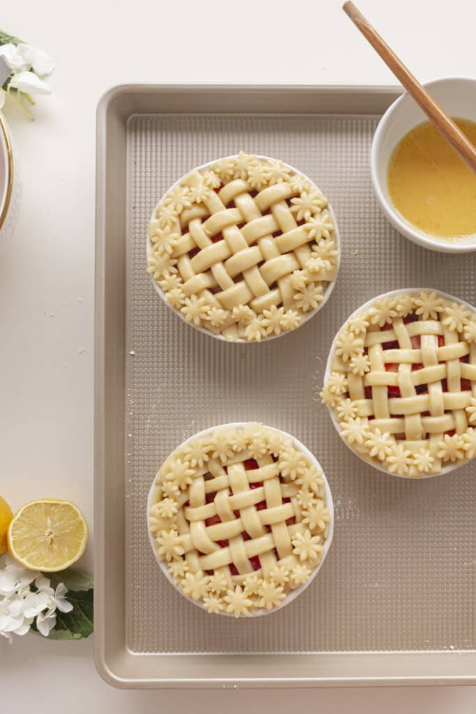 lattice top on pies with egg wash on a baking sheet