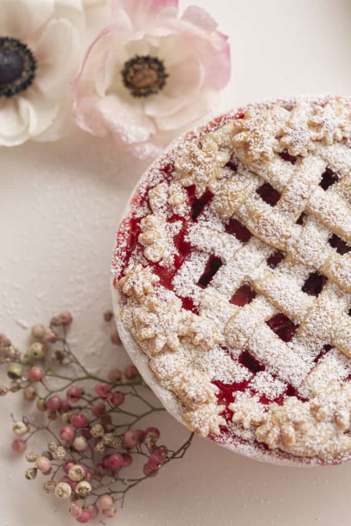 close up of a strawberry pie with lattice top and flowers